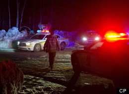 Police vehicles block a road just outside the town of Chertsey, Que., Sunday, March 17, 2013, during a search for escaped prisoners. THE CANADIAN PRESS/Graham Hughes