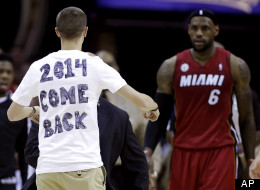 A fan runs out on the court towards LeBron James during an NBA basketball game in Cleveland on Wednesday, March 20, 2013.