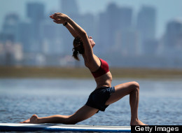 Claudia Townsend enjoys a paddleboard yoga session at Adventure Sports Miami on July 10, 2011 in Miami, Florida. The paddle board is said to give the body's core more of a workout then in a gym since the platform is unstable and one must use the muscles to remain balanced on the board. (Photo by Joe Raedle/Getty Images)