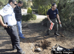 A bomb technician collects the remains of a rocket launched from Gaza Strip falling close to Sderot on April 3, 2013.  (Photo by DAVID BUIMOVITCH/AFP/Getty Images)