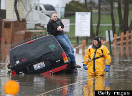 A rescue official stands with a motorist stuck in water during heavy rains and flooding in Round Lake Heights, Illinois, Thursday, April 18, 2013, at Pontiac Court and Tomahawk Trail. (Joe Shuman/Chicago Tribune/MCT via Getty Images)
