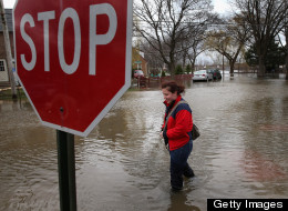 A woman walks down a flooded sidewalk on April 19, 2013 in Des Plaines, Illinois. (Photo by Scott Olson/Getty Images)