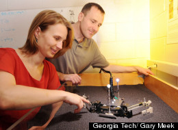 Georgia Tech associate professor Daniel Goldman and researcher Nicole Mazouchova watch FlipperBot move through a bed filled with poppy seeds.