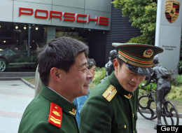 Chinese paramilitary soldiers walk past a showroom for Porsche luxury cars next to their barracks in Shanghai, 05 March 2007.