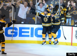 Patrice Bergeron #37 of the Boston Bruins celebrates with Brad Marchand #63 and Zdeno Chara #33 after scoring in overtime against the Pittsburgh Penguins in Game Three of the Eastern Conference Final during the 2013 NHL Stanley Cup Playoffs at TD Garden on June 5, 2013 in Boston, Massachusetts. (Photo by Brian Babineau/NHLI via Getty Images)