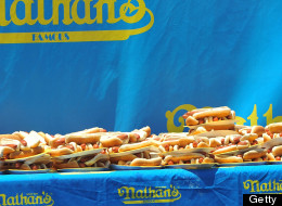 Joey Chestnut (L) of San Jose, California celebrates winning the annual International July Fourth Hot Dog Eating Contest by holding a plate of 66 hot dogs and buns with an unidentified official on July 4, 2007, at the original Nathan's Famous restaurant in the Coney Island section of Brooklyn, NY. Chestnut won by eating 66 hot dogs in 12 minutes. AFP PHOTO/Stan HONDA