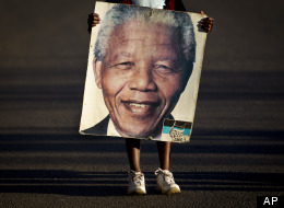 Lehlogonolo Nkosi, 7, holds a portrait of Nelson Mandela as she and her grandmother Florah, 52, unseen, leave after visiting the entrance where flowers and get-well messages have been left by well-wishers at the Mediclinic Heart Hospital where former South African President Nelson Mandela is being treated in Pretoria, South Africa Wednesday, July 3, 2013. (AP Photo/Ben Curtis)