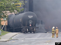 Smoke rises from railway cars that were carrying crude oil after derailing in downtown Lac-Mégantic, Que., Saturday, July 6, 2013. The Chicago-based railroad company that operated the train involved in the Lac Megantic disaster has an accident rate much worse than the average for U.S. railroads, a newspaper report said Tuesday. (THE CANADIAN PRESS/Paul Chiasson)
