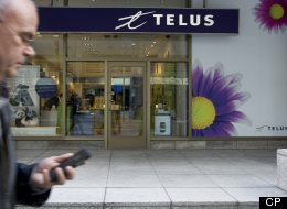 A cell phone user passing a Telus store in Toronto on Monday, April 1, 2013. A long-simmering cold war between Canada's big telecom firms and consumer advocates has turned into a hot war over the contentious subject of whether or not Canadians are being ripped off on their wireless bills. (Peter Power / The Globe and Mail)