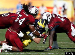 Receiver Drew Dileo #9 of the Michigan Wolverines gets a first down on a fake punt as defenders Chaz Sutton #90, Shaq Wilson #54 and Reginald Bowers #47 of the South Carolina Gamecocks close in for the tackle during the Outback Bowl Game at Raymond James Stadium on January 1, 2013 in Tampa, Florida.  (Photo by J. Meric/Getty Images)