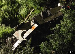 A bus lies on its side after plunging off a highway near Avellino, southern Italy, eraly Monday, July 29, 2013. (AP Photo/Salvatore Laporta)