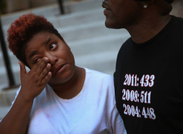 Brianna Williams wipes away tears as she tells Willie Williams Jr. about her boyfriend Darius Oliver following a prayer vigil outside the Uptown Baptist Church August 21, 2013 in Chicago, Illinois. Oliver, one of five people who were shot while standing in front of the church on Aug. 19, died early Friday. On Willie Williams Jr.'s shirt are annual murder tallies for the city of Chicago.  Williams Jr.'s son was murdered in 2006. (Photo by Scott Olson/Getty Images)