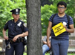 A NYPD officer and a protestor look on as civil rights, legal advocates and residents hold a press conference June 18 in New York outside One Police Plaza to discuss planned legal action challenging the city police department's surveillance of businesses frequented by Muslim residents and area mosques. (TIMOTHY CLARY/AFP/Getty Images)