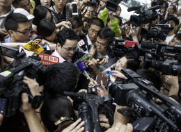 Lan He (C), legal advisor for the family of Li Tianyi -- the son of a Chinese singer charged with rape, according to state media -- is surrounded by a group of journalists before the trial of Li's case in Haidian court in Beijing on August 28, 2013. Li Tianyi, the son of a Chinese general Li Shuangjiang, went on trial on August 28 over his involvement in an alleged gang rape, state media said, in a case that sparked public outrage.  CHINA OUT     AFP PHOTO        (Photo credit should read STR/A