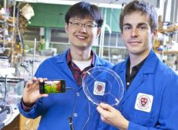 Jeong-Yun Sun (left) and Christoph Keplinger (right), Harvard University, demonstrate their transparent ionic speaker.
