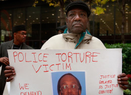 Aaron Cheney demonstrates outside the federal courthouse where former Chicago Police Commander Jon Burge was attending a hearing on charges he obstructed justice and committed perjury for lying while under oath during a 2003 civil trial about decades-old Chicago police torture allegations October 27, 2008 in Chicago, Illinois. The city's tab for settlements in Burge torture cases has hit about $85 million. (Photo by Scott Olson/Getty Images)