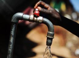 Kenya, Nairobi, woman turning on a tap at a water distribution site in the Kibera slum