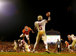 Jameis Winston #5 of the Florida State Seminoles throws a pass as Vic Beasley #3 of the Clemson Tigers tries to stop him during their game at Memorial Stadium on October 19, 2013 in Clemson, South Carolina.