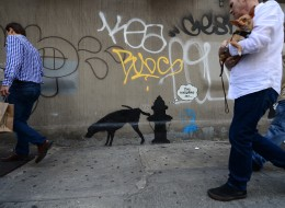 People walk by a street art graffiti by elusive British artist Banksy, as part of his month-long Better Out Than In exhibit, in New York, October 3, 2013. Banksy will be attempting to host an entire show on the streets of New York during a month residency. (EMMANUEL DUNAND/AFP/Getty Images)