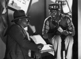 circa 1933:  American actors and comedy partners Freeman Gosden (L) and Charles Correll perform in blackface makeup as Amos 'n' Andy. Gosden smokes a cigar while facing Correll, who wears a 'TAXI' cap and holds a twenty dollar bill in his hand.  (Photo by Hulton Archive/Getty Images)