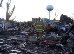 WASHINGTON, IL - NOVEMBER 17: Jeremy Janssen of Mackinaw Fire Department walks through debris along Elgin Avenue after a tornado struck on November 17, 2013 in Washington, Illinois. Several tornadoes touched down across the Midwest today with at least three people reported dead in Illinois. (Photo by Tasos Katopodis/Getty Images)