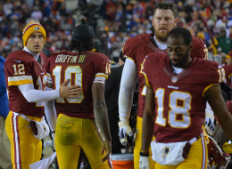 Washington Redskins quarterback Kirk Cousins (12) consoles Washington Redskins quarterback Robert Griffin III (10) following a 24-17 loss against the New York Giants at FedEx Field on December 1, 2013 in Landover, Md. (Photo by Ricky Carioti/The Washington Post via Getty Images)
