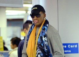 Former US NBA basketball player Dennis Rodman (R) waits to check in at Beijing's international airport on December 19, 2013.  Rodman is on a visit to North Korea from December 19 to 23.    AFP PHOTO / WANG ZHAO        (Photo credit should read WANG ZHAO/AFP/Getty Images)