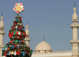 Backdropped by a mosque, ornaments bearing notes and wishes decorate a Christmas tree outside a church in Dubai, 25 December 2007. (KARIM SAHIB/AFP/Getty Images)