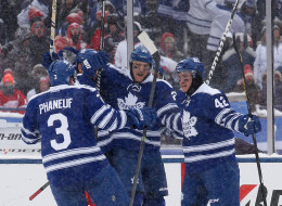 James van Riemsdyk #21 of the Toronto Maple Leafs celebrates his second-period goal against the Detroit Red Wings with teammates Dion Phaneuf #3 and Tyler Bozak #42 during the 2014 Bridgestone NHL Winter Classic at Michigan Stadium on Jan. 1 in Ann Arbor, Mich.