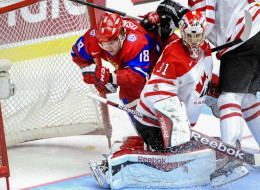 Russia's Vyacheslav Osnovin, left, is checked into the net behind Canada's goalie Zachary Fucale during the World Junior Hockey Championships bronze match between Canada and Russia at Malmo Arena in Malmo, Sweden, Sunday, Jan. 5, 2014. (AP Photo/Ludvig Thunman, TT News Agency)