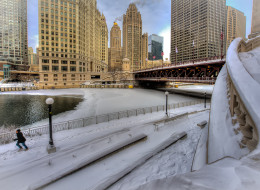 Partially iced over Chicago River and Riverfront walk covered by snow after