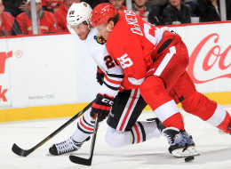 Danny DeKeyser #65 of the Detroit Red Wings bodies Brandon Saad #20 of the Chicago Blackhawks off the puck during an NHL game on January 22, 2014 at Joe Louis Arena in Detroit, Michigan. Detroit defeated Chicago 5-4 in a shootout (Photo by Dave Reginek/NHLI via Getty Images)