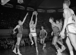 Tom Gola #15 of the Philadelphia Warriors shoots the ball against Chuck Noble #5 and Corky Devlin #8 of the Fort Wayne Pistons during Game Three of the NBA Finals on April 3, 1956 at the Philadelphia Civic Center in Philadelphia, Pennsylvania.