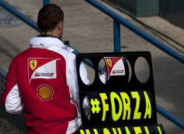 A member of the Ferrari team holds a board with a message of support for seven-time World Champion Michael Schumacher during the Formula One pre-season test days at Jerez racetrack in Jerez on January 29, 2014.