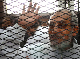Egyptian Muslim Brotherhood's supreme guide, Mohamed Badie waves from inside the defendants cage during the trial of Brotherhood members on February 3, 2014 AFP PHOTO / AHMED GAMIL        (Photo credit should read AHMED GAMIL/AFP/Getty Images)
