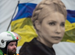 An anti-government protester stands in front of a portrait of jailed former Ukrainian Prime minister Yulia Tymoshenko, on  Maidan square in Kiev, on February 13, 2014. Ukraine has been in chaos since November when President Viktor Yanukovych ditched an EU trade and political pact in favour of closer ties with Moscow, its former Soviet master. AFP PHOTO / MARTIN BUREAU        (Photo credit should read MARTIN BUREAU/AFP/Getty Images)