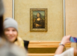 A historian has revealed his new theory on why Mona Lisa is smiling. Here, visitors take pictures of Leonardo da Vinci 'Mona Lisa' inside the Louvre museum on Feb. 28 in Paris.