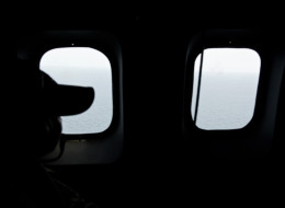 Search for Flight MH370: A crew member looks out the windows from a Malaysian Air Force CN235 aircraft during a search to find the missing Malaysia Airlines flight (MOHD RASFAN/AFP/Getty Images)