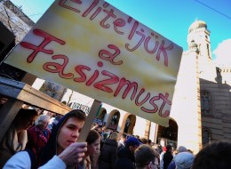 A participant holds a placard with a text 'We are against Fascism' in front of the local synagogue of Budapest on March 19, 2014 during a commemoration of the victims of Nazis occupation. (ATTILA KISBENEDEK/AFP/Getty Images)