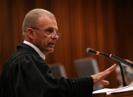 State prosecutor, Gerrie Nel, looks on while cross-examining South African Olympic and Paralympic sprinter Oscar Pistorius during his trial at the North Gauteng High Court in Pretoria on April 9, 2014. Pistorius insisted on April 9 he never intended to kill his girlfriend, as the prosecution began tearing into his version of events on that fateful night.