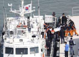 South Korean Coast Guard officers carry the body of a passenger aboard the Sewol ferry which sank in the water off the southern coast, upon its arrival at a port in Jindo, South Korea, Monday, April 21, 2014. (AP Photo/Ahn Young-joon)