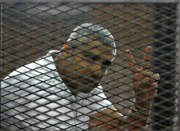 Canadian-Egyptian journalist Mohamed Fahmy gestures from the defendant's cage during a sentencing hearing in a courtroom in Cairo, Egypt, Monday, June 23, 2014. An Egyptian court on Monday convicted three journalists from Al-Jazeera English and sentenced them to seven years in prison each on terrorism-related charges, bringing widespread criticism that the verdict was a blow to freedom of expression. The three, Australian Peter Greste, Canadian-Egyptian Mohammed Fahmy and Egyptian Baher Mohammed