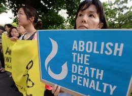Members of civic groups hold banners denouncing the death penalty during a demonstration in front of the Justice Ministry in Tokyo on June 26, 2014. Japan carried out its first execution of the year on June 26 when it hanged a man for a triple murder, the ninth prisoner to be put to death since the conservative government of Shinzo Abe took power in 2012.       AFP PHOTO/Toru YAMANAKA        (Photo credit should read TORU YAMANAKA/AFP/Getty Images)