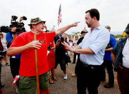 Adam Kwasman, a Tea Party patriot running for congress (R), has a heated discussion with an anti-immigration activist during a protest along Mt. Lemmon Road in anticipation of buses carrying  illegal immigrants on July 15, 2014 in Oracle, Arizona. (Sandy Huffaker/Getty Images)