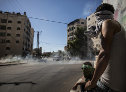 Palestinian supporters of Hamas take shelter while clashing with Israeli security forces on July 25, 2014 near Ramallah, West Bank.(Andrew Burton/Getty Images)