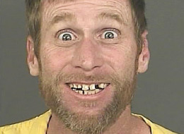 A Sept. 23, 2014 photo provided by the Denver District Attorney's Office shows Michael Whitington with a broad, toothy smile and eyes open wide after his Sept. 23, 2014 arrest in Denver. Whitington was captured after allegedly trying to flee a bank robbery in Denver. He has been charged with one count of robbery and is due to appear in court on Tuesday, Sept. 30, 2014, to be advised of the charge. (AP Photo/Denver District Attorney's Office)
