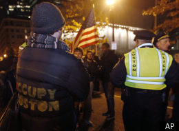 Occupy Boston protestors and Boston Police officers wait in the middle of Atlantic Avenue in Boston, early Friday Dec. 9, 2011. Boston Mayor Thomas Menino said Thursday that Occupy Boston protesters must leave their encampment in the city's financial district by midnight Thursday or face eviction by police. (AP Photo/Charles Krupa)