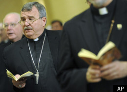 Bishop John R. Manz, second left, Auxiliary Bishop of Chicago, prays during the U.S. Conference of Catholic Bishops' annual fall meeting Nov. 16, 2010 in Baltimore.