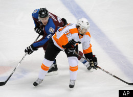 Colorado Avalanche center Paul Stastny, left, and Philadelphia Flyers left wing Harry Zolnierczyk, right, battle for control of the puck in the second period of an NHL hockey game on Monday, Dec. 19, 2011, in Denver. (AP Photo/Chris Schneider)