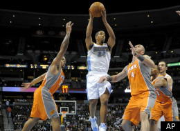 Denver Nuggets point guard Andre Miller (24) goes up for a shot against Phoenix Suns point guard Shannon Brown (26) and Marcin Gortat (4) from Poland during the third quarter of an NBA preseason basketball game in Denver, Tuesday, Dec. 20, 2011. (AP Photo/Jack Dempsey)